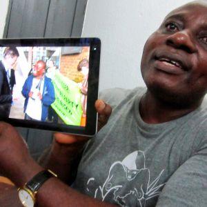 afrikkalainen mies näyttää kuvaa tabletilta