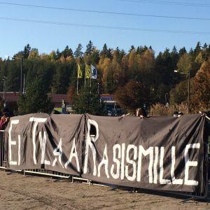 """Ett lakan med texten """"Ei tilaa rasismille"""" på en demonstration."""