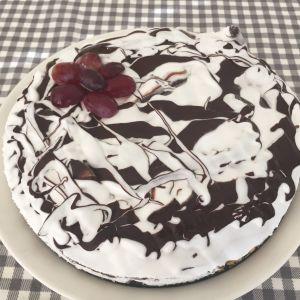 Valkoruskearadiallinen kakku, jonka päällä on viinirypäleitä.