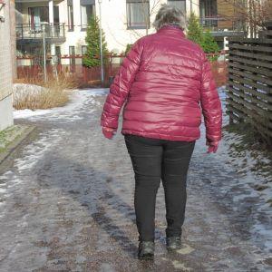 Polvikipuinen nainen kävelee liukkaalla talvisella tiellä.