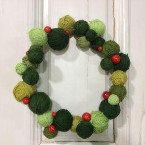 Krans gjord av gröna garnnystan, dekorerad med röda träkulor