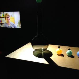 glasföremål på bord och tv-skärm i mörkt rum.