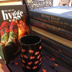 En bok om hygge med ullstrumpor på pärmen, en mugg med danska flaggor.