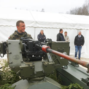 En polsk soldat tittar närmare på den estniska obemannade Milrem-bandvagnen som här är utrustad med en kulspruta.