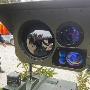 Yles medarbetare Gustaf Antell syns i spegelbilden på en detalj av en kulspruta monterad på ett obemannad bandvagn.