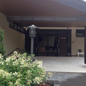 Ingången till Raasepori Resort, buskar framför, ståtligt.