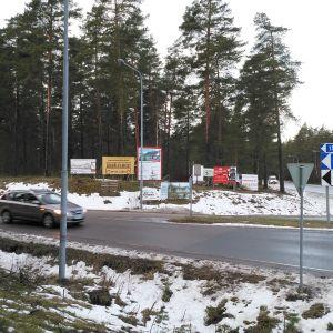 bil i vägkorsning med reklamskyltar