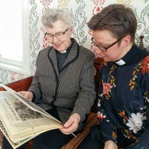 Ulla Östman och Malin Lindblom tittar på tidningsklipp från 1988 då de första kvinnorna prästvigdes.