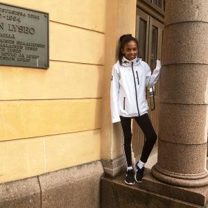 brunhyad flicka med långt svart hår står vid gul väg och granitpelare