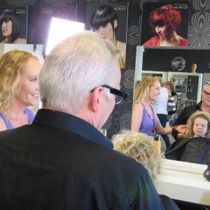 Kampaaja laittaa Tuhkimotarinoiden Lindan hiuksia.