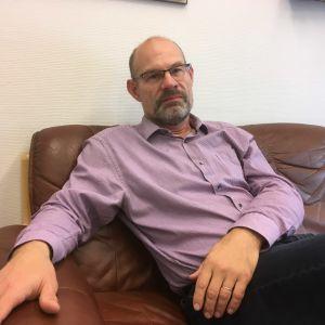 medelålders man med skägg, glasögon, lila skjorta, sitter i brun lädersoffa och tittar allvarligt på fotografen