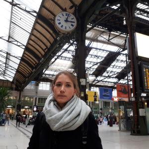 En ung kvinna på en tågstation ser allvarligt in i kameran.