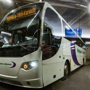 Pohjolan Liikennes buss står parkerad vid en hållplats i Kampen i Helsingfors.