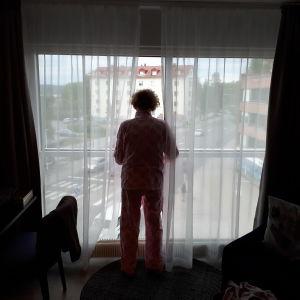 nainen katsoo ulos hotellihuoneen isosta ikkunasta valoa vasten