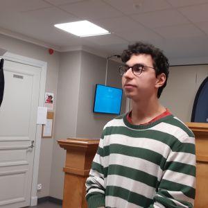 ung mörkhårig man med svarta glasögon och grönvitrandig blus står i skolkorridor
