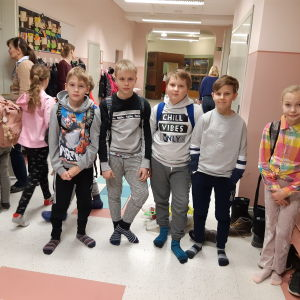 Fem barn i tioårsåldern står i skolkorridor med andra barn och lärare i bakgrunden.