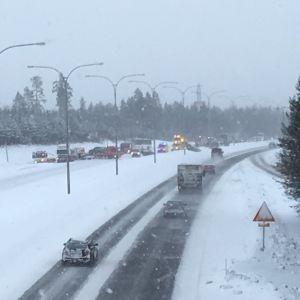 Krockade bilar, en ambulans och bärgningsfordon syns på en snöig landsvägssträcka.