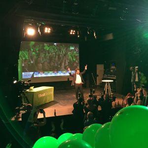 De grönas partiledare Ville Niinistö på scen på partiets valvaka i Helsingfors efter kommunalvalet 2017. Niinistö ler med hela ansiktet och lyfter bägge armarna i en segergest.
