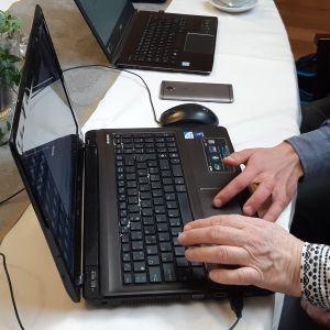 en äldre och en yngre hand ligger på tangenterna till en svart dator. En annan dator syns i bakgrunden och lite av en grönväxt