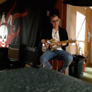 ung man med skärmmössa sitter och spelar elgitarr i källarutrymme. På väggen bakom honom finns en öppen dörr till höger och en stor svart lakan med en dödsskalle