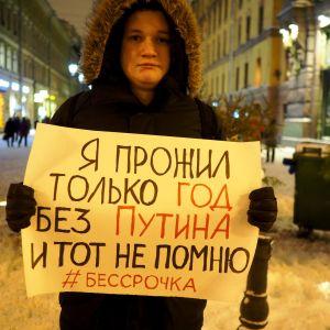 Nuori mielenosoittaja kannattelee Putinin-vastaista kylttiä Pietarissa