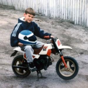 Handbollsspelaren Nico Rönnberg som liten pojke, han istter på en liten moped med hjälm i famnen.