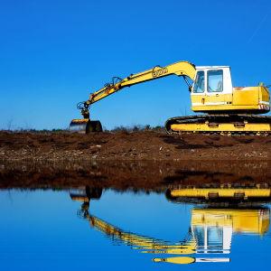 En grävmaskin gräver i torvjorden vid vattnet. Grävmaskinen speglas i vattenytan.