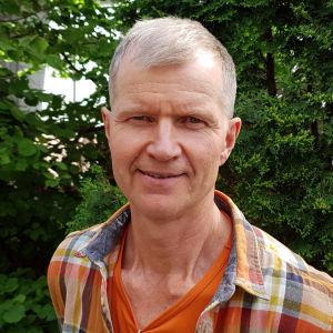 Näyttelijä Taisto Reimaluoto vihreän puskan edessä.