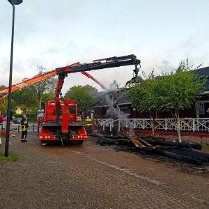 En cafébyggnad som röker. Utanför står två utryckningsfordon, den ena har en kran som lyfter brandskadat virke från byggnaden.