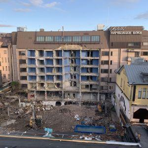 Man ser hotellets bakre yttervägg som är borta och hotellrummen gapar tomma som ett stående schackspel.