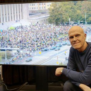 Thomas Wallgren i Svenska Yles lokaler framför en tv-skärm. På tv-bilden syns klimatdemonstranter utanför riksdagen den 27 september.