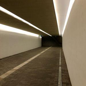 En tunnel med vita väggar och asfalterat golv.