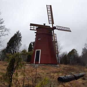 En röd väderkvarn på ett berg i Ingå.