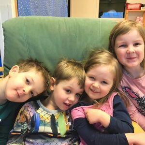 Fyra glada dagisbarn i en grön länstil.