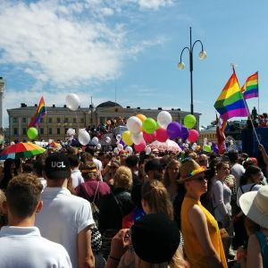 Människor med ballonger och regnbågsflaggor på Senatstorget.