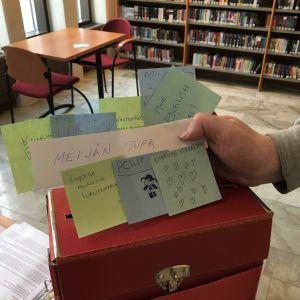Käsi pitelee lappusia, joihin on kirjoitettu toiveita kirjastolle.