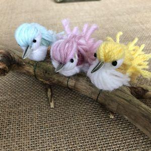 Tre små fåglar gjorda av garn sitter på en kvist på bordet