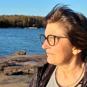 Kvinna med brunt, halvlångt hår och glasögon kisar mot solnedgången vid klippig strand