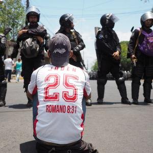 Man med vit skjorta sitter på asfalten med ryggen mot kameran, framför står poliser i hjälmar.