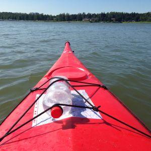 Vattenflaska och sjökort fastspända på en röd kajak i Esbo innerskärgård.