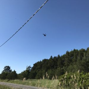 Gränsbevakningens helikopter flyger över åkrar och träd på Satava för att släcka en brand.