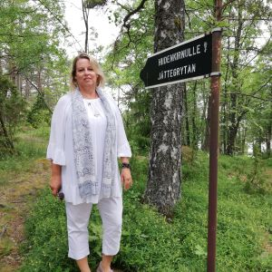 """En kvinna med halvlångt blont hår och kjusa kläder står ute vid en skylt där det står """"Hiidenkirnulle Jättegrytan""""."""