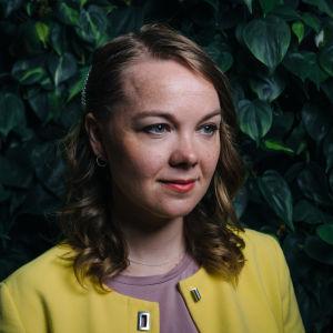 porträtt på Katri kulmuni i gul tröja och lockigt hår med ett pärlspänne i.