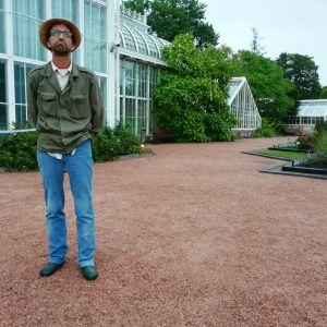 En man i hatt och mossgrön jacka står i Botaniska trädgården i Kajsaniemi i Helsingfors. Växthuset i bakgrunden.