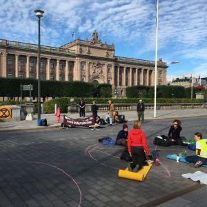 Demonstranter sitter på gata och bro utanför riksdagshuset i Stockholm.