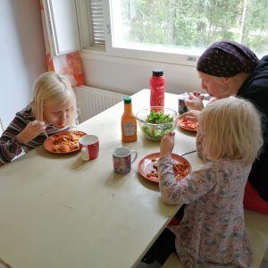Holopaisen perhe syömässä vegaanilasagnea pöydän ääressä.