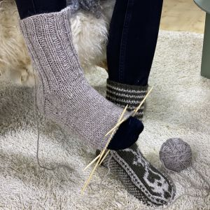 En halvfärdig stickasocka provas på en fot