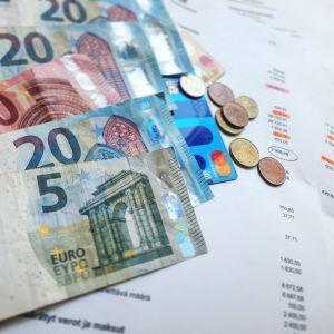 Euroseteleitä, kolikoita ja papereita, jossa näkyy eurosummia