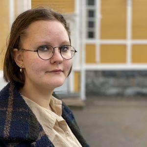 Anetta Kukkonen seisoo koulun sisäpihalla.