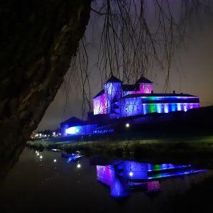 Hämeen vanha linna sinipunaisessa juhlavalaistuksessa.